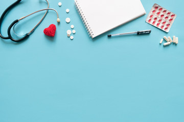 Medical mockup with stethoscope, pills drugs, red heart, white notepad on blue background. Doctor work place flat lay, top view with copy space