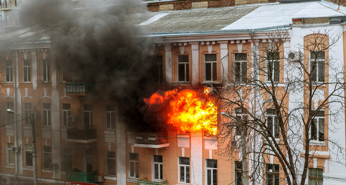 Odessa, Ukraine - Dec. 29, 2016:  fire in an apartment building. Strong bright light and clubs, smoke clouds window of their burning house. Firefighters extinguish fire in house. Work on fire stairs