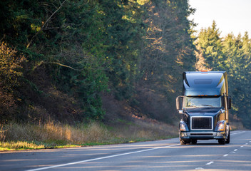 Big rig black modern semi truck transporting semi trailer with commercial cargo running on the road with trees on side