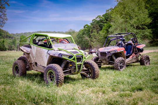 Two Muddy UTV Side by Side Off Road Vehicles