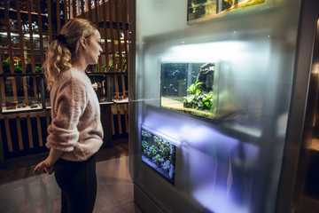 Blonde girl looking a fish tank