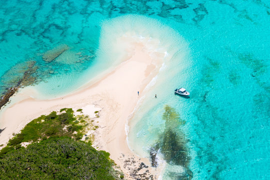 Tourists, divers, snorkelers, jet boat, an idyllic empty sandy beach of remote island, azure turquoise blue lagoon, West Coast barrier reef, aerial view. New Caledonia, Melanesia, South Pacific Ocean