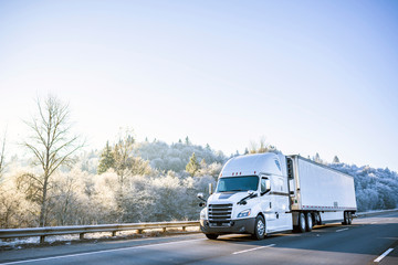 Big rig white technological semi truck with reefer semi trailer going on the winter road with frost trees on the hill Wall mural
