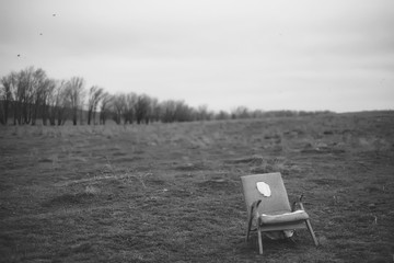 A hill with trees in black and white. Vintage armchair in the middle of the field. Gray landscape of nature and old furniture. Armchair with wooden handles. Autumn bare trees. Dry grass on the field.