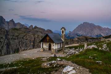 Breathtaking summer scenic landscape view of iconic Cappella degli Alpini chapel while sunrise in famous Tre Cime di Lavaredo mountains in the Dolomites mountain range, South Tirol Alps, Italy, Europe
