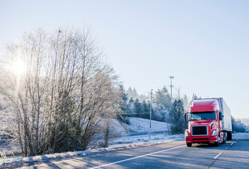 Bright red big rig semi truck with refrigerator semi trailer transporting cargo on straight winter highway frosty hill trees