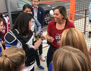 Student Hannah August, shares a laugh with U.S. National Softball Team catcher Sahvanna Jaquish, during a visit to Agoura High School, in Agoura Hills, California