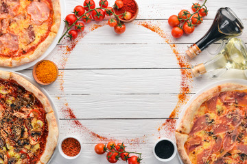 Foto auf Acrylglas Pizzeria A set of Italian pizza. Italian cuisine. On a white wooden background. Free copy space. Top view.