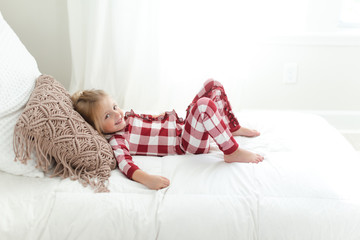 Young smiling girl wearing pajamas lying down on a bed