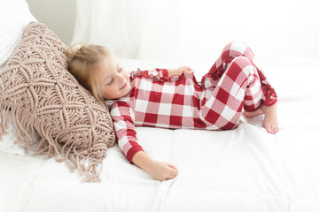 Young girl in pajamas lying on a bed