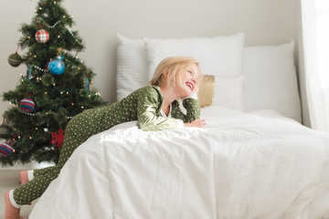 Smiling young girl leaning on a bed next to a Christmas tree