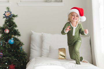 Young girl wearing a Santa hat next to a Christmas tree