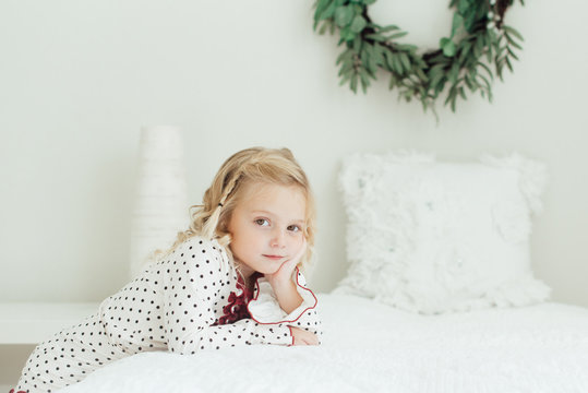 Young girl leaning on a bed