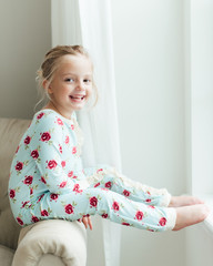 Smiling young girl sitting on the armrest of a couch