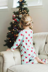 Young girl looking at a Christmas tree while sitting on a couch