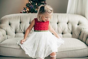 Young girl in a dress sitting on a couch
