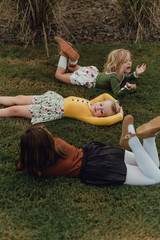 Three young girls laying on the grass