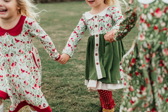 Three girls in floral dresses playing