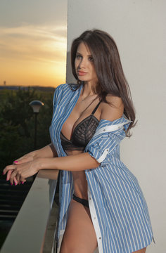 Beautiful young woman in blue unbuttoned shirt over black lingerie posing outdoor with sunset sky in background. Perfect body sensual long hair brunette on high heels posing on ledge in twilight
