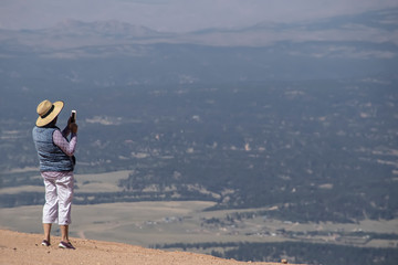 Background with room for text - tourist woman takes cellphone picture of valley below from high up on mountain - Pikes Peak Colorado