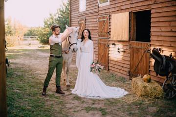 boho-style newlyweds standing near horse on ranch