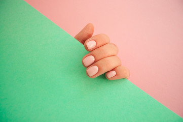 Young woman's hand with beautiful manicure on pink and turquoise background with copyspace.