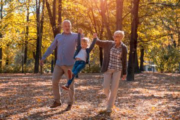 Happy grandparents and granddaughter having fun in autumn park together