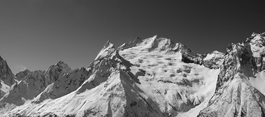 Wall Mural - Panorama of snowy covered mountain peaks and clear sky at sun winter day