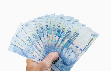 South African banknotes in hand.