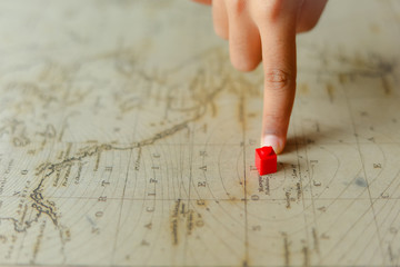 Hand with a red marker on a map