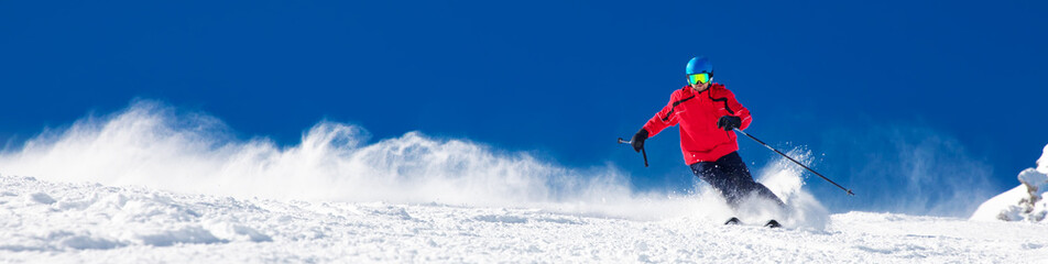 Stores à enrouleur Glisse hiver Man skiing on the prepared slope with fresh new powder snow