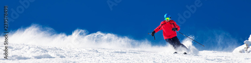 Fototapete Man skiing on the prepared slope with fresh new powder snow