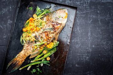 Traditional BBQ parrotfish with mango salsa as top view on a black board copy space right