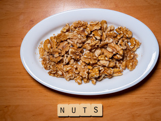 A plate of peeled nuts with the word. Top view