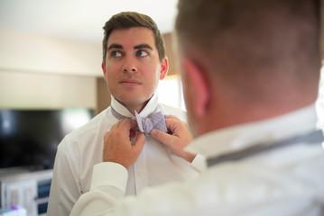 a man helps his friend tie his bow tie
