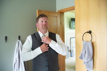 A man ties his tie in the mirror