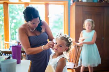 a mom puts earrings in her daughters ears