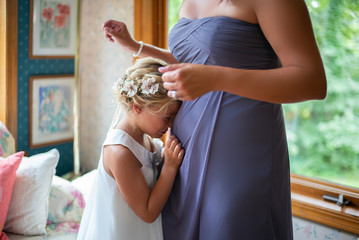 A flower girl hugs her mom