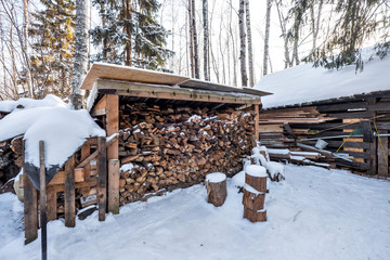Firewood stacked in piles, covered with snow. cutted trunks in a alpine hut in winter forest