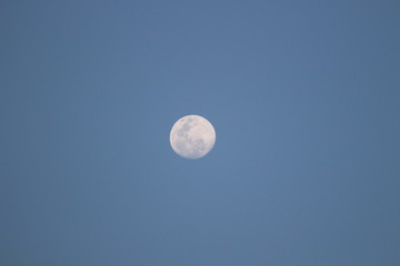 Almost full white moon on a blue sky