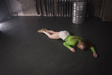 Lifeless unconscious woman lying on a factory floor
