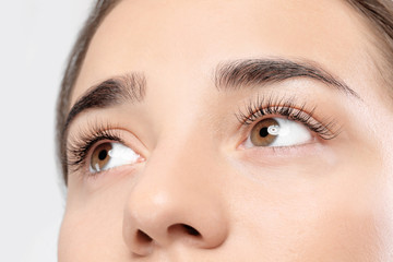 Young woman with beautiful eyelashes on light background, closeup view