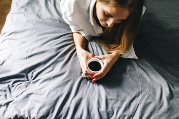 Top view of a Young girl in a white shirt holding a mug of coffee lying on the bed . Young woman drinking coffee at home in her bed, start, concept in the morning, early in the morning. Stylish Toned