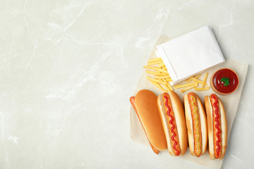 Composition with hot dogs, french fries and sauce on table, top view. Space for text