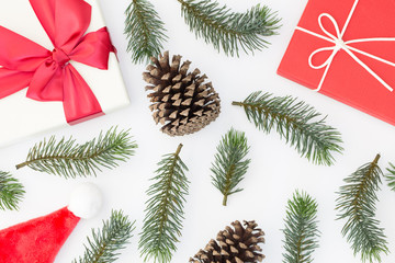 Top view of Christmas composition, gift box, pine cones, fir branches on white background