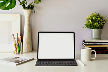 Front view workspace with blank screen modern tablet and home office supplies