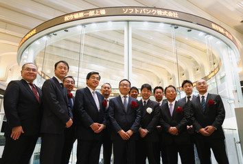 SoftBank Corp. President and CEO Ken Miyauchi poses for a photograph with the company executives during a ceremony to mark the company's debut on the Tokyo Stock Exchange in Tokyo