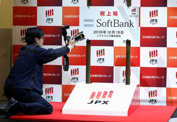 A photographer takes a photo of the logo of SoftBank Corp. during a ceremony to mark the company's debut on the Tokyo Stock Exchange in Tokyo