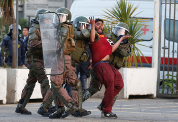A Chilean dockworker is detained by riot police during a protest against port operator TPS in Valparaiso