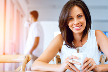 Happy young woman with cup of tea or coffee
